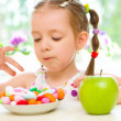 Child choosing between apple and sweets — Stock Photo