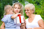 Great-grandmother offering present — Stock Photo