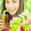 Girl drinking grapes juice outdoors — Stock Photo