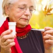 Old woman taking her temperature — Stock Photo