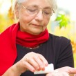 Senior woman holding a pill in her hand — Stock Photo #33718529
