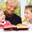 Great-grandmother reading a book for grandchildren — Stock Photo