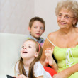 Grandmother with her grandchildren are watching TV — Stock Photo #35171235