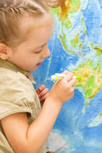 Child smiles by world map — Stock Photo