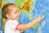 Child smiles by world map — Stockfoto