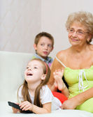 Grandmother with her grandchildren are watching TV — Stock Photo