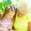 Grandmother with granddaughter drawing — Stock Photo