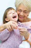 Granddaughter with granddaughter knitting — Stock Photo