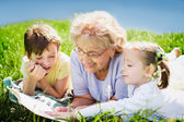 Grandmother reading book to grandchildren outdoors — Stock Photo
