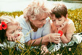 happy grandmother with grandchildren outdoors — Stock Photo