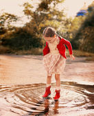 Kid jumping into a puddle — Stock Photo