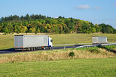 Two trucks on the road in the countryside — Stock Photo