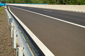 Empty asphalt highway with concrete crash barrier in the middle — Stock Photo