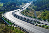 Empty highway between forests in the landscape — Stock Photo