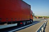 Oncoming red trucks on empty highway in the countryside — Foto Stock