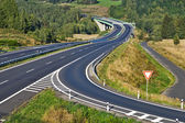 Access road to the highway between forests in the landscape — Stock Photo