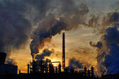 Chimneys and dark smoke over chemical factory at sunset — Stock Photo