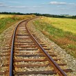 Rusty railroad tracks on a railway embankment between meadows — Stock Photo