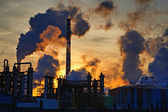 Chimneys and dark smoke over chemical factory at sunset — Foto de Stock
