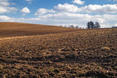 Undulating plowed field in early spring — Stock Photo
