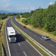 Highway passing through the countryside, truck and passenger cars — Stock Photo