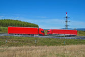 Spring landscape with highway and oncoming red trucks passing around pylon — Foto Stock