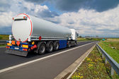 A tanker truck on the highway leading through the countryside — Stock Photo