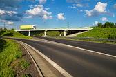 Bridge over an empty highway, going over the bridge truck — Stockfoto