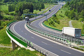 The highway between woods, electronic toll gates, three moving trucks — Stock Photo