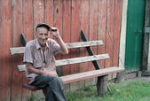 An old villager sitting on a bench — Stock Photo