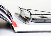 телефон, ручка и очки на ноутбуке — Стоковое фото