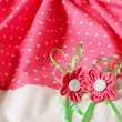 Fabric background with artificial flowers — Stock Photo