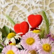 Stock Photo: Bouquet of chamomiles and two hearts