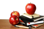 Notebooks, pens and apples on a table — Stock Photo