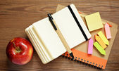 Notebooks, pens, stickers and apple — Stock Photo