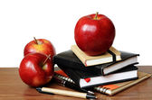 Notebooks, pens and apples on a desk — Stock Photo