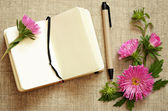 Notebook and a pen with asters composition — Stock Photo