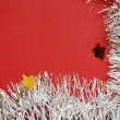 White tinsel on red background — Stock Photo #34506563