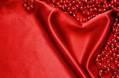 Red satin and beads — Stock Photo