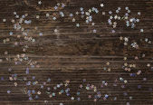 Small stars on dark wooden background — Stock Photo
