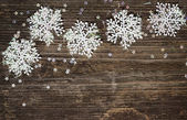 Snowflakes on dark wood — Foto Stock