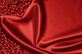 Red satin drapery and beads — Stock Photo