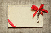 Greeting card with red ribbon and a key — Stock Photo