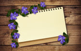 Notepad and periwinkle flowers — Stock Photo