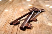 Old keys over a grunge pine table top background — Stock Photo