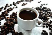 Koffiebonen en kopje koffie uitwerking voor brunch hotel tijd — Stockfoto