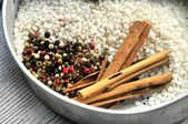 Rice and seasoning ingredients cinammon and pepper corns — Stock Photo
