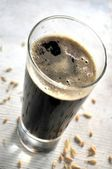 Frosty glass of black beer — Stock Photo
