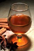 Spirit cognac or brandy cup with spice anis and cinammon sticks — Stock Photo