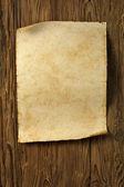 Alte pergament auf holzwand — Stockfoto
